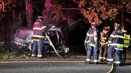 Firefighters at the scene of a fatal single-car