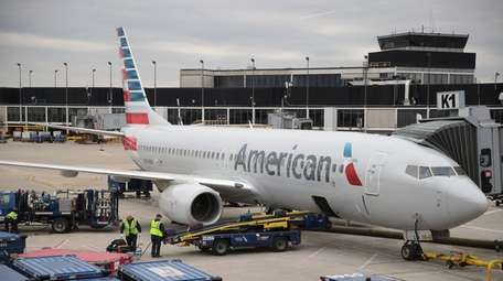 Workers load luggage onto an American Airlines aricraft