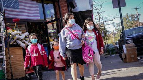 Pedestrians in masks pass a store Oct. 15