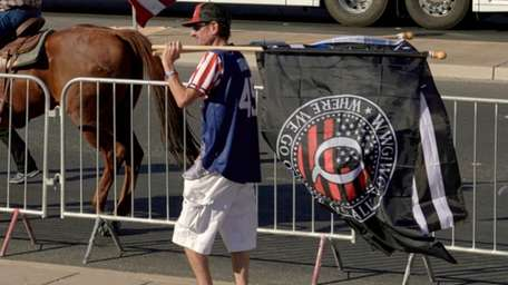 """A man holds a """"QAnon"""" flag, outside the"""