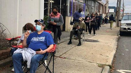 People wait in line on Merrick Road in