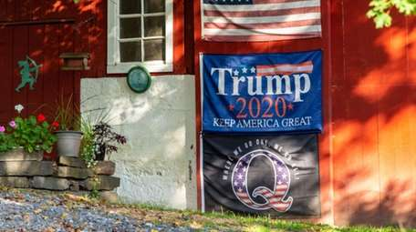 An American flag, a Trump re-election flag, and