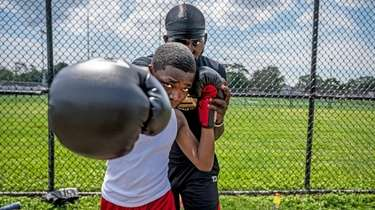 USA boxing coach Jizzixious Bishop helping his student