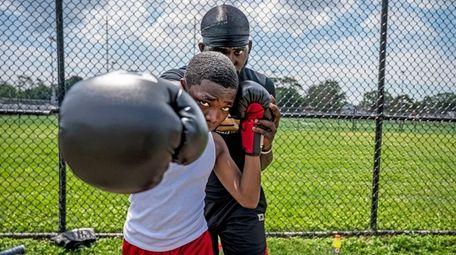 USA boxing coach Jizzixious Bishop helping his student