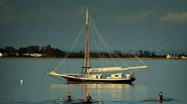People row past a moored Sailboat through the