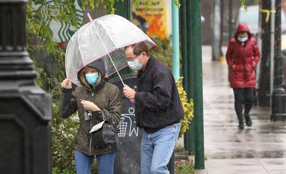 A couple shares an umbrella as they walk