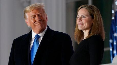 President Donald Trump and Amy Coney Barrett stand