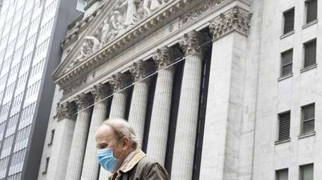 A man wearing a protective mask walks Monday