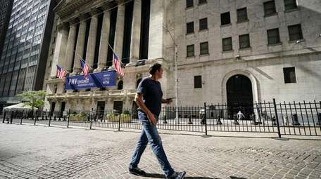 A pedestrian passes the New York Stock Exchange