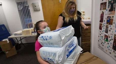 Isabel helps her mom, Jody Sommer, gather supplies
