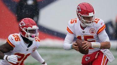 Kansas City Chiefs quarterback Patrick Mahomes, right, drops