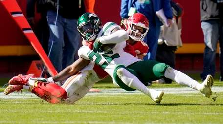 Jets running back La'Mical Perine (22) is tackled