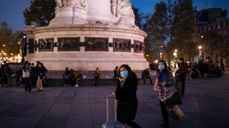 Tourists wearing protective masks walk on Republique square