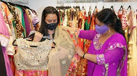Poonam Jain, right, owner of Vastra Boutique, with
