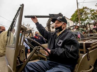 Anthony Catalano climbs into a WWII Jeep brought