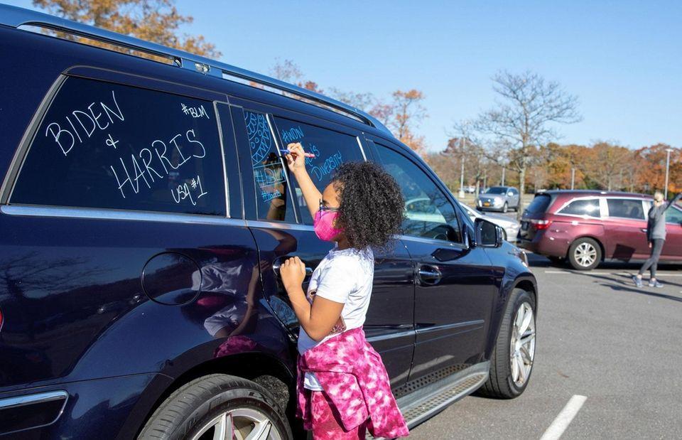 Mia Douglas, 11, decorates car at pro-Biden Victory