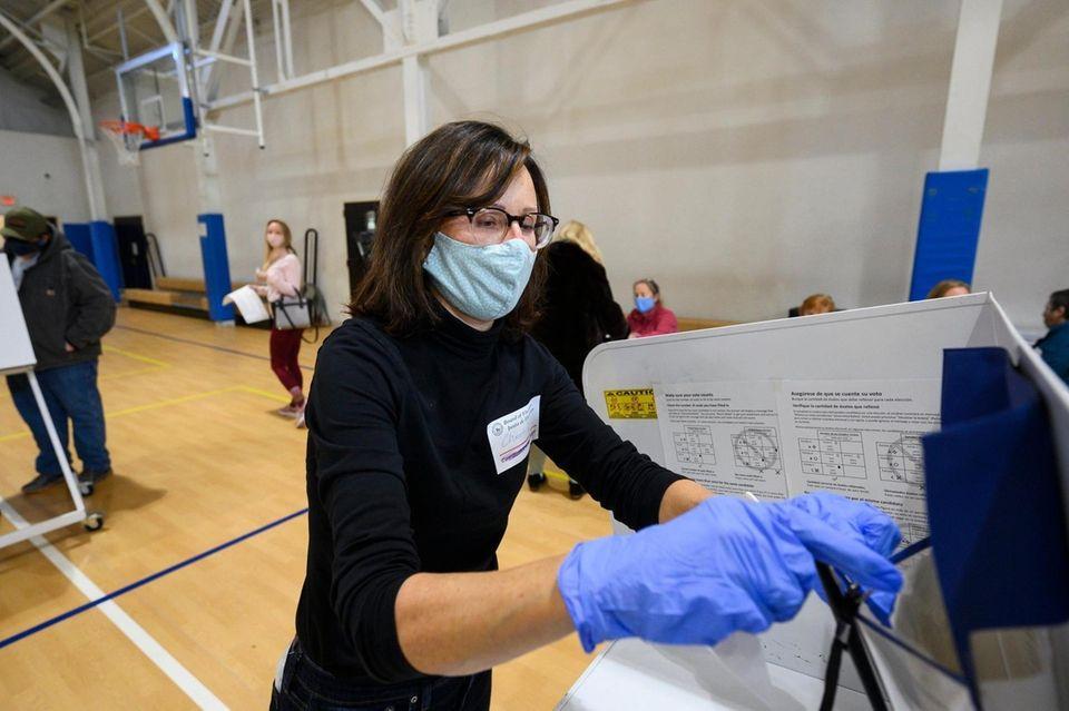 Poll inspector Christine Lefler, from Montauk, sanitizes a