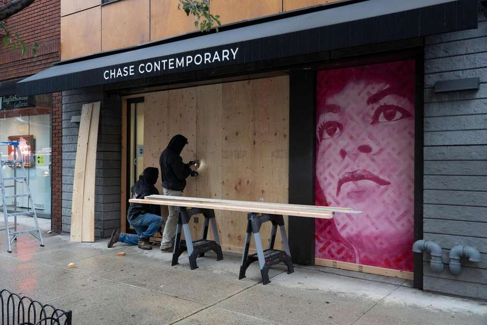 An art gallery is boarded up on 10th