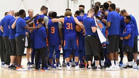 Knicks players and coaches huddle during training camp