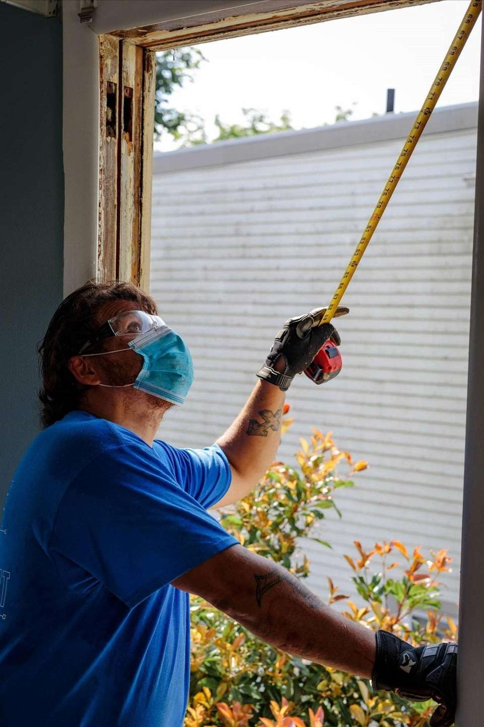 A Power Home Remodeling operations team member measures