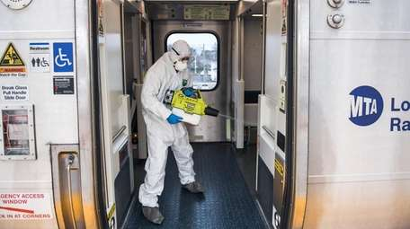 A Long Island Rail Road employee disinfects a