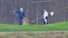 President Donald Trump, left, plays a round Sunday