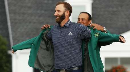 Dustin Johnson is awarded the Green Jacket by