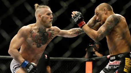 Conor McGregor, left, and Dustin Poirier, exchange hits