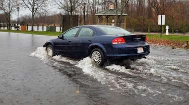 A car plows through standing water near the