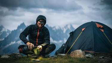 A hardy hiker prepares a hot beverage with
