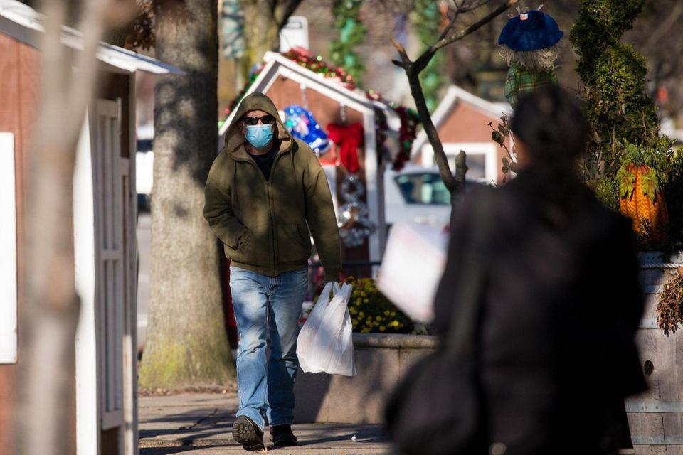 A man wears a mask while walking along