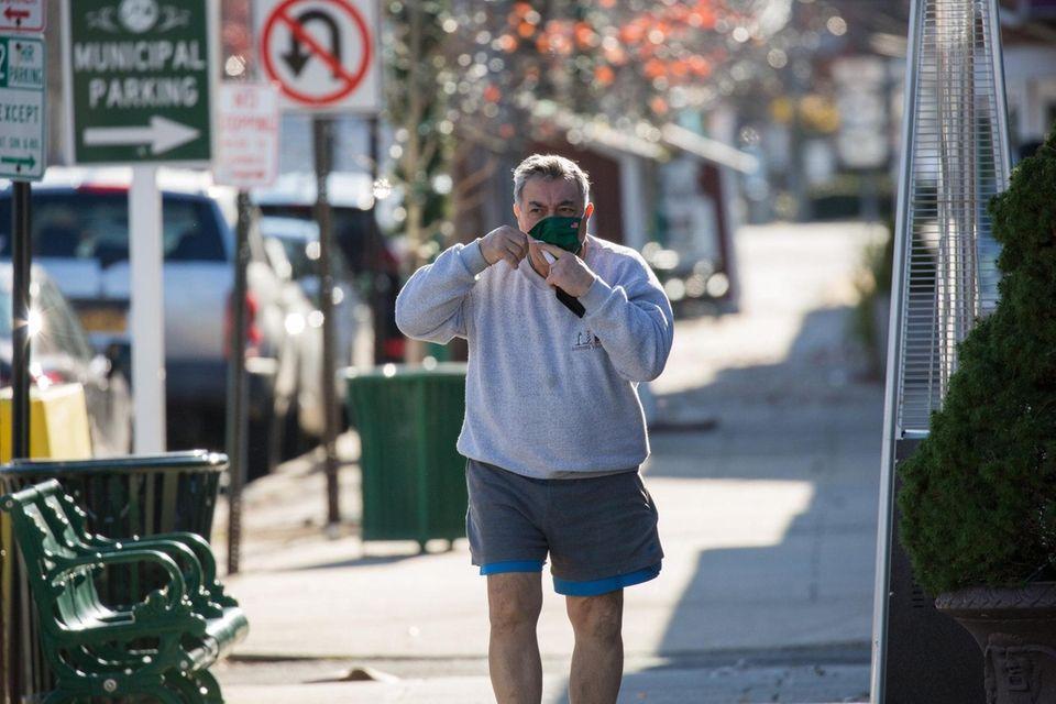 A man masks up walking along Park Boulevard