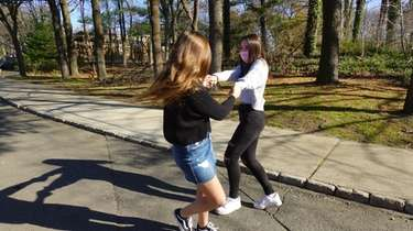 Ava Golio, 15, right, of Westbury, plays with