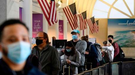 Thanksgiving travelers wait in line Wednesday at a