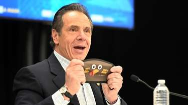 Gov. Andrew M. Cuomo holds up a new