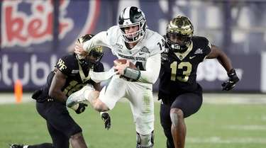 Michigan State quarterback Brian Lewerke tucks the ball