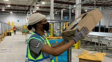 An Amazon worker sorts packages in the company's