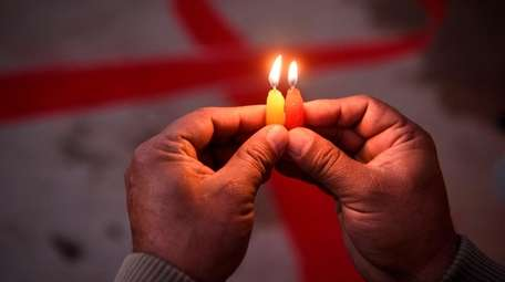 A volunteer lights candles forming the shape of