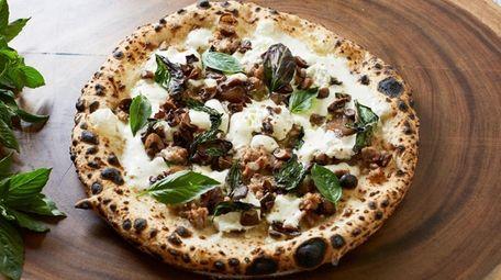 The cannolo pie topped with mozzarella, ricotta, sausage,