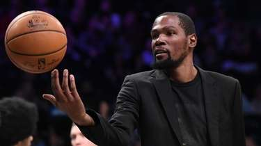 The Nets' Kevin Durant tosses the ball during