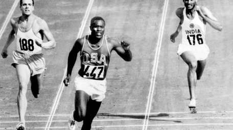 Rafer Johnson of the United States, center, finishes