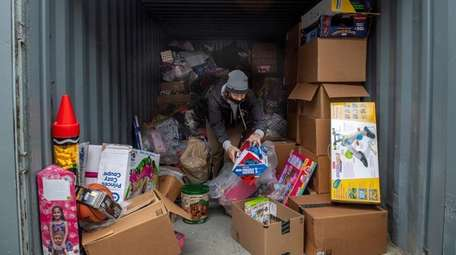 John Theissen organizes items at his foundation's Wantagh
