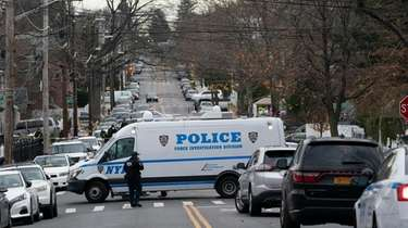 Police vehicles are parked near the scene of