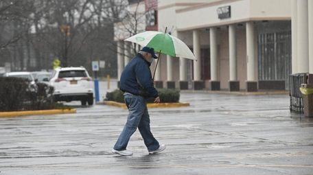A man heads through the rain to a