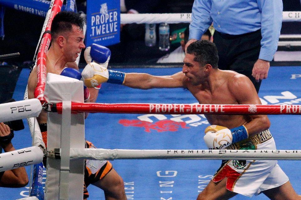 Francisco Santana, left, falls against the ropes after