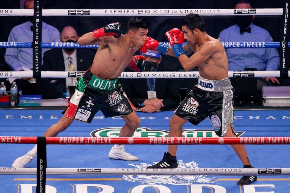 Miguel Flores, left, takes a punch from Eduardo
