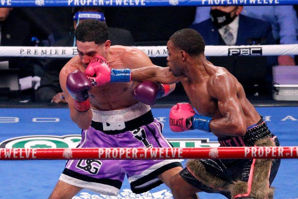 Danny Garcia, left, is hit by Errol Spence