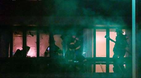 Firefighters work to extinguish a blaze at the