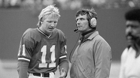 Giants quarterback Phil Simms, left, talks to coach