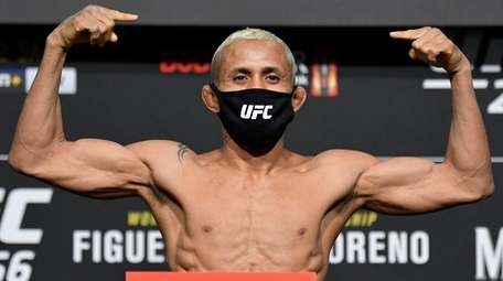 Deiveson Figueiredo poses on the scale during the